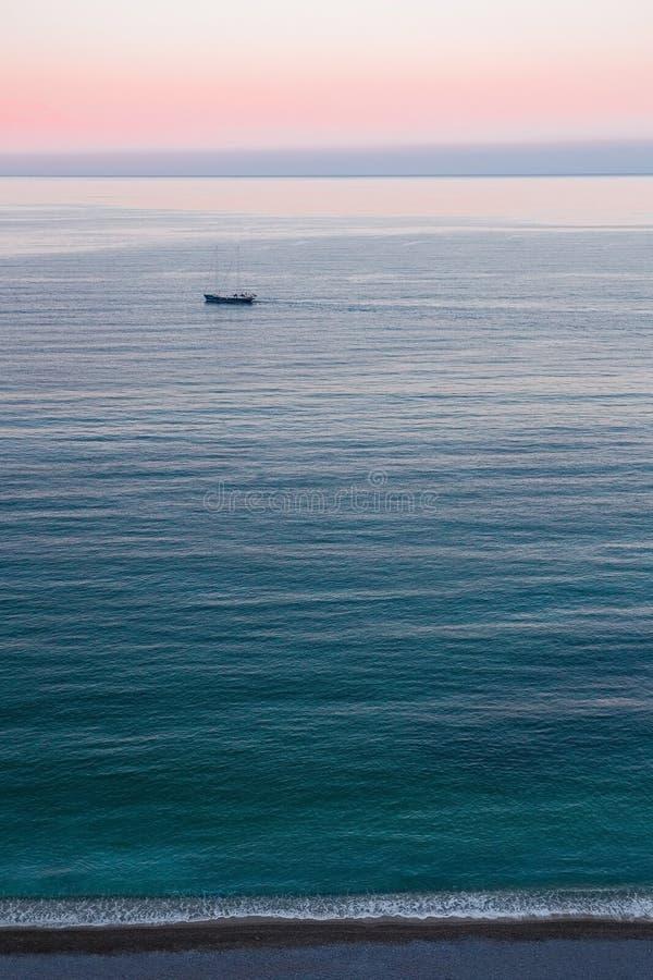 Por do sol cor-de-rosa sobre a costa e o navio imagens de stock royalty free