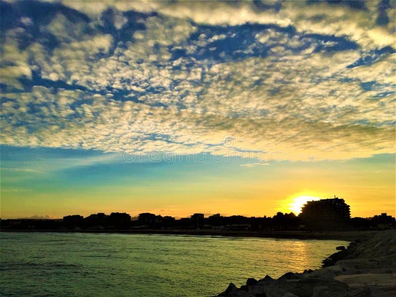 Por do sol, cores, céu, nuvens, água e mar em Civitanova Marche, Itália imagens de stock royalty free