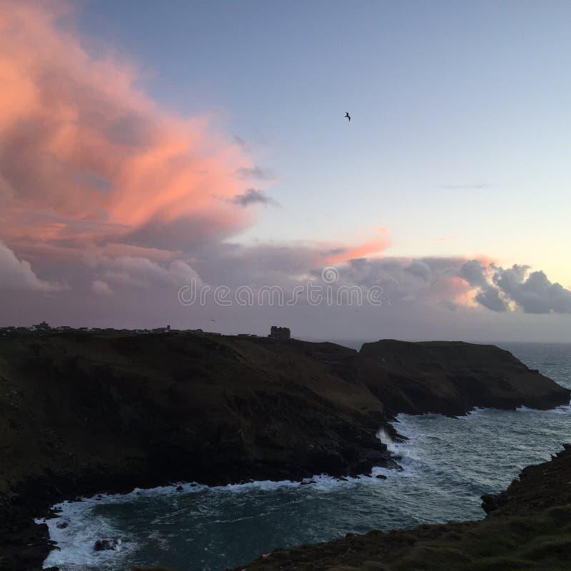 Por do sol costal com nuvens cor-de-rosa foto de stock