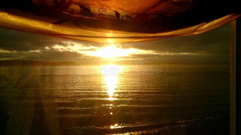 Por do sol da água, através de uma janela curtained fotografia de stock royalty free