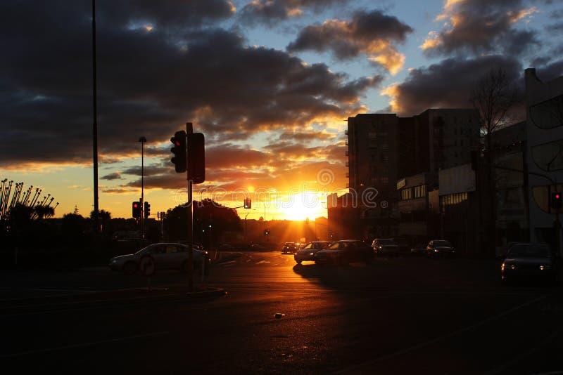 por do sol da cidade em um dia nebuloso com os carros no juction do sinal de tráfego foto de stock royalty free