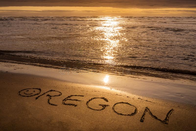 Por do sol da costa de Oregon, texto escrito na praia imagens de stock