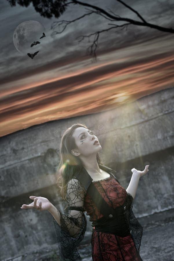 Por do sol da mulher da forma do vampiro assustador imagens de stock