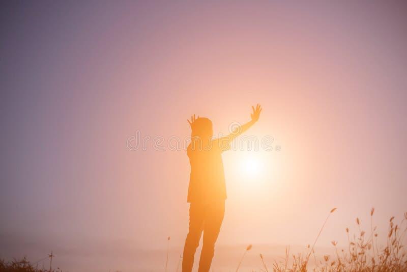 Por do sol das mãos da mulher da silhueta imagem de stock