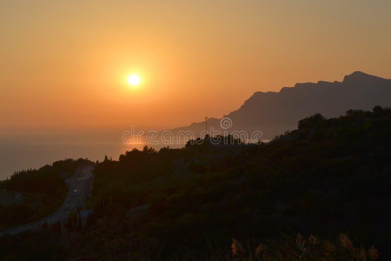 Por do sol, sol de ajuste sobre o mar e montanhas imagem de stock