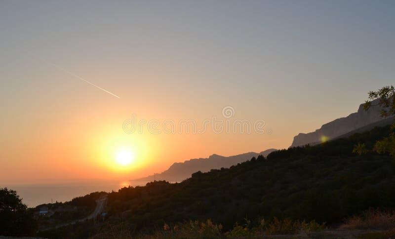 Por do sol, sol de ajuste sobre o mar e montanhas, cores roxas fotos de stock royalty free