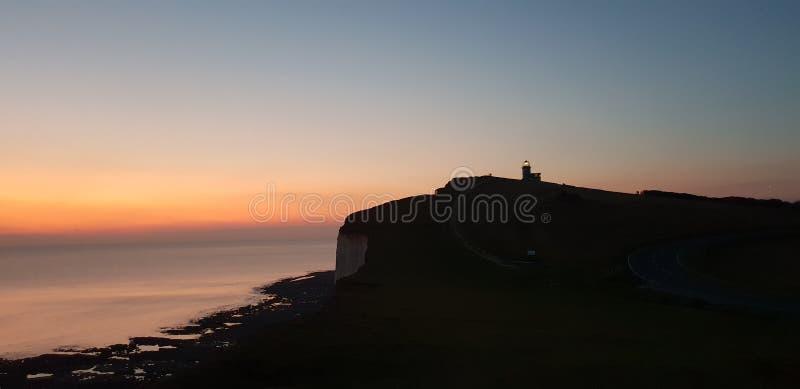 Por do sol de Eastbourne Sussex do farol da candonga do Belle foto de stock royalty free