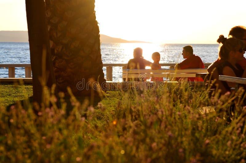 Por do sol de observação da família na praia imagens de stock royalty free