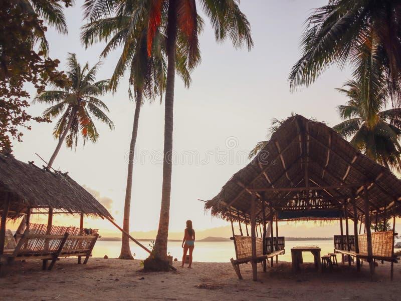 Por do sol de observação da mulher com as palmeiras na ilha de Candaraman em Balabac Filipinas fotos de stock royalty free