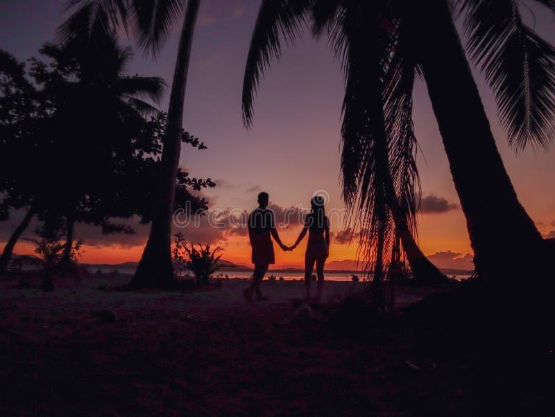 Por do sol de observação dos pares com as palmeiras na ilha de Candaraman em Balabac Filipinas fotografia de stock