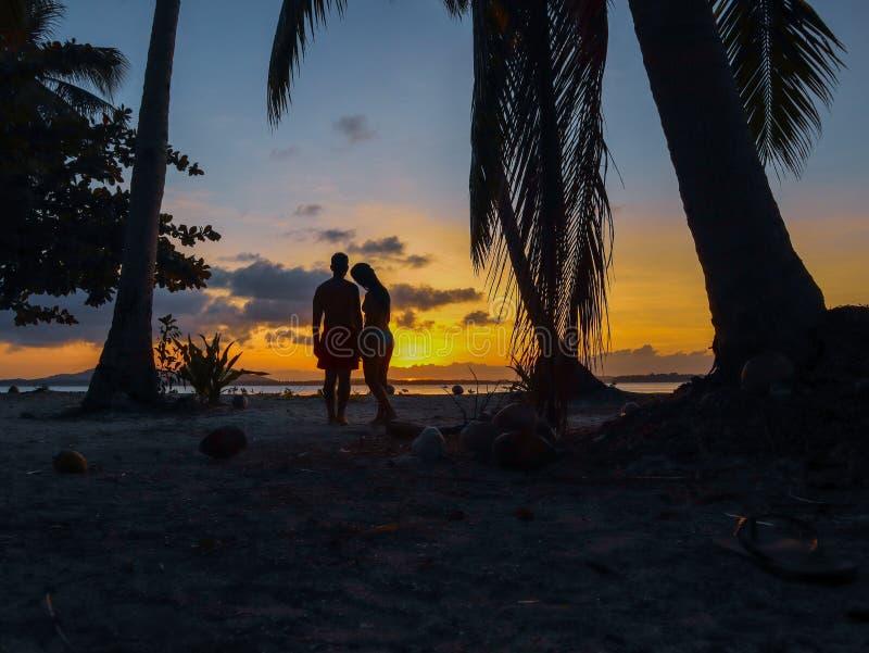 Por do sol de observação dos pares com as palmeiras na ilha de Candaraman em Balabac Filipinas imagens de stock