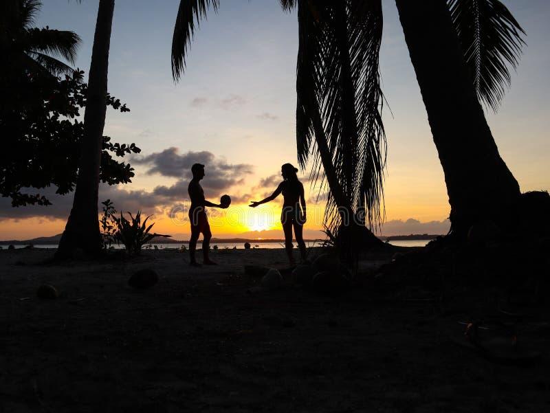 Por do sol de observação dos pares com as palmeiras na ilha de Candaraman em Balabac Filipinas imagem de stock