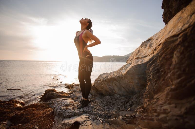 Por do sol de observação fêmea do montanhista de rocha sobre o mar imagens de stock royalty free