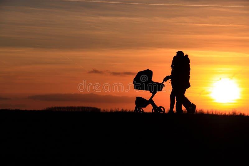 Por do sol de passeio do carro de bebê dos pares imagens de stock royalty free