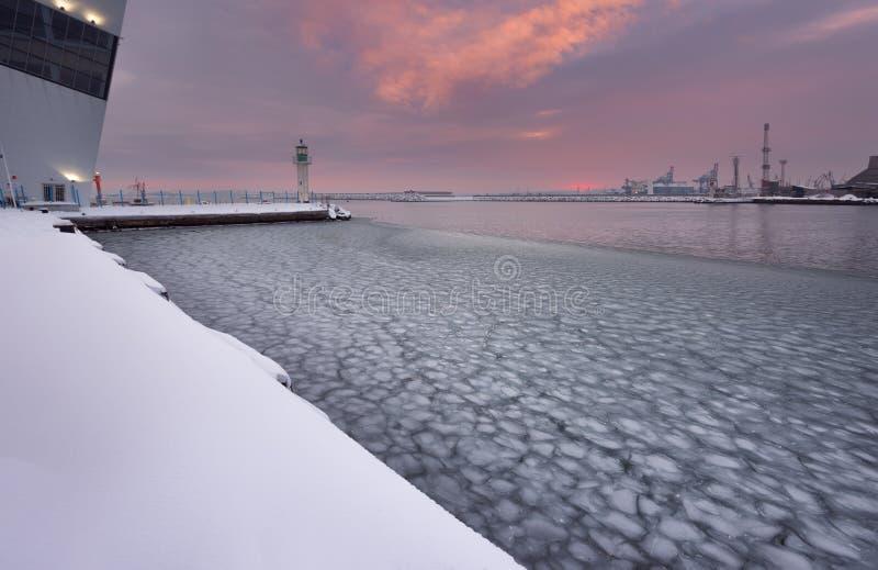 Por do sol do fogo do inverno e mar congelado na estação marinha, Burgas, Bulgária imagem de stock