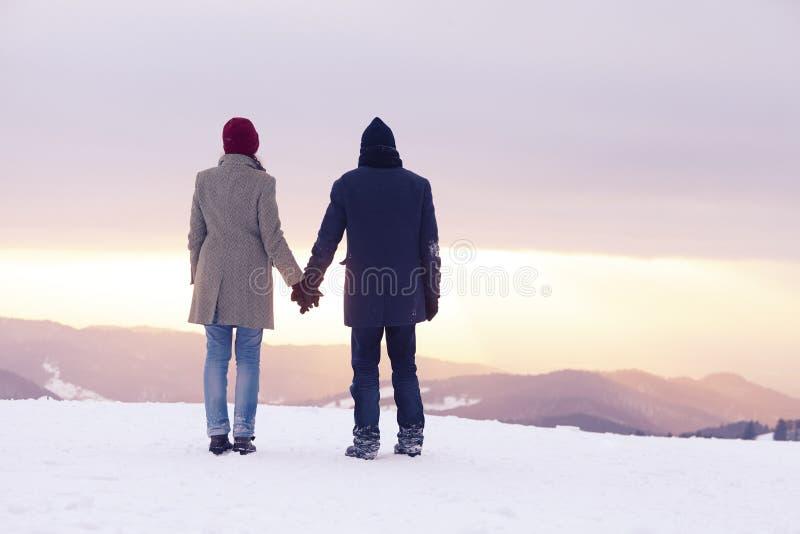 Por do sol do inverno da mulher do homem foto de stock royalty free