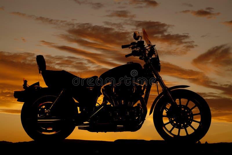 Por do sol do lado da motocicleta da silhueta foto de stock