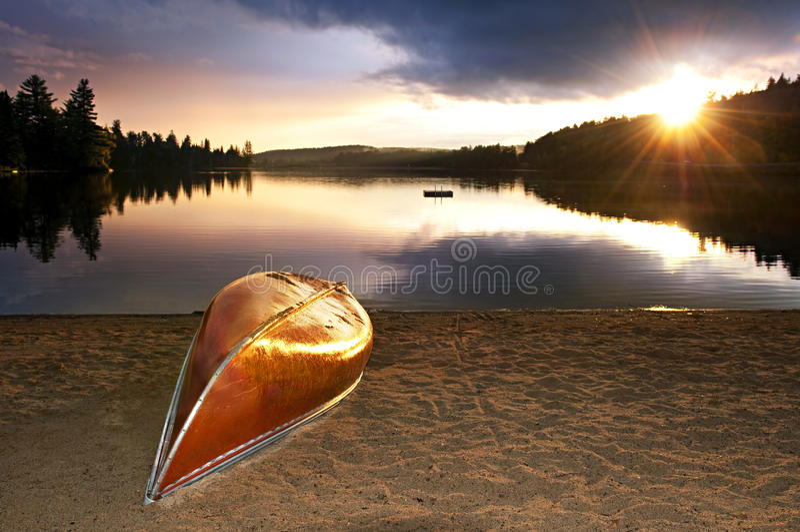 Por do sol do lago com a canoa na praia foto de stock