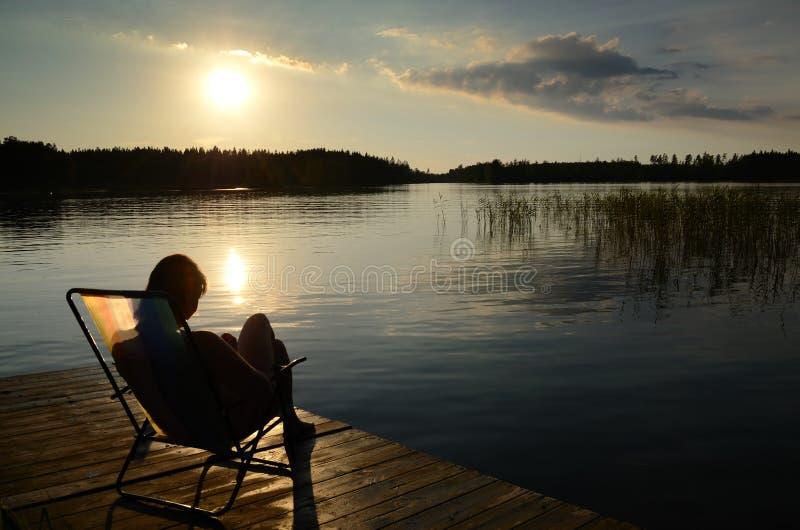 Por do sol do lago da cadeira de plataforma fotografia de stock royalty free