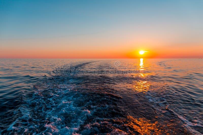 Por do sol do mar com traço do navio fotos de stock royalty free