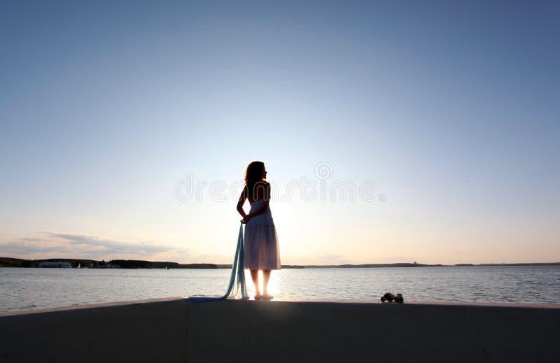 Por do sol do relógio da menina foto de stock