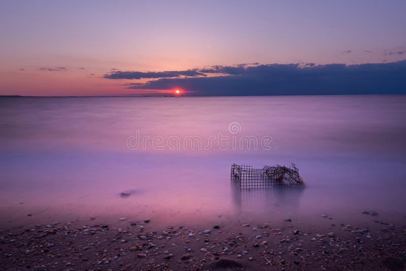 Por do sol do Seascape com lavado acima da gaiola do caranguejo fotos de stock
