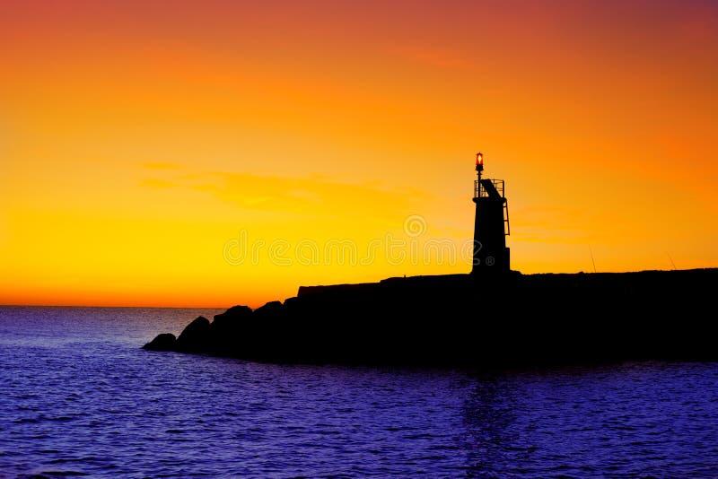Por do sol dourado do nascer do sol no farol vermelho da baliza do mar imagens de stock royalty free