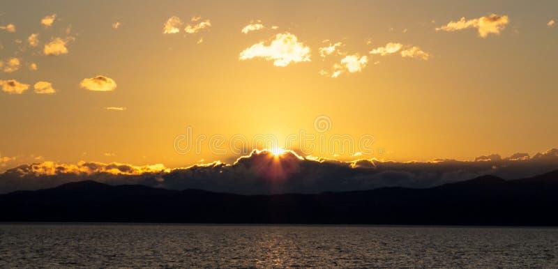 Por do sol dourado sobre as montanhas e as nuvens imagens de stock royalty free