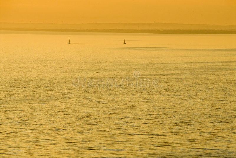 Por do sol dourado sobre o mar fotografia de stock royalty free