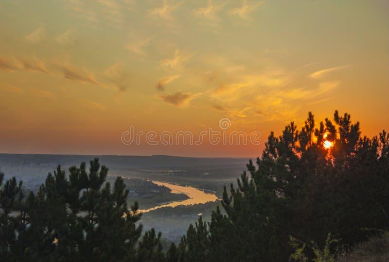 Por do sol dramático sobre o rio nevoento de Dnister com pinheiros e colo fotos de stock royalty free
