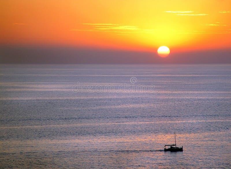 Por do sol e barco fotografia de stock royalty free