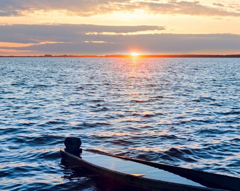 Por do sol e barco afogado no banco do lago do verão fotos de stock royalty free