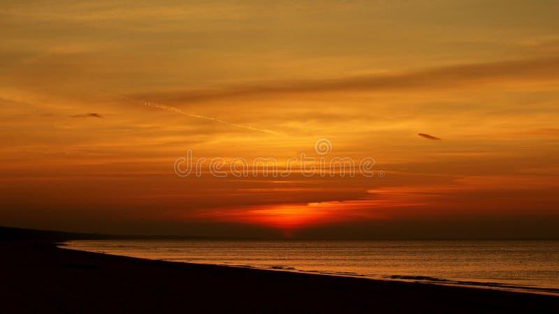 Por do sol e céu alaranjado sobre a costa de mar imagens de stock