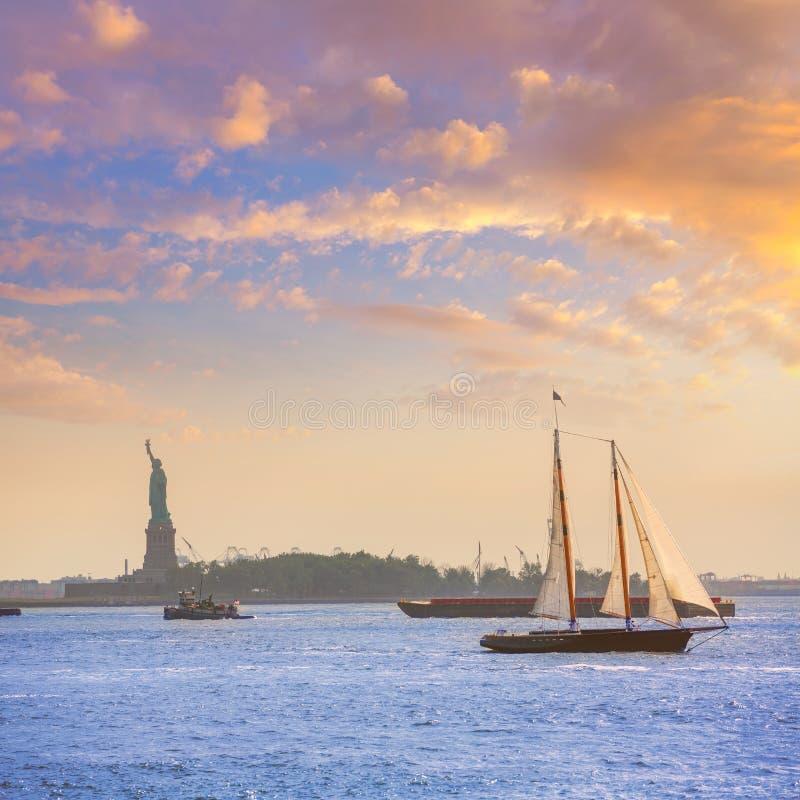 Por do sol e estátua da liberdade do veleiro de New York fotografia de stock royalty free