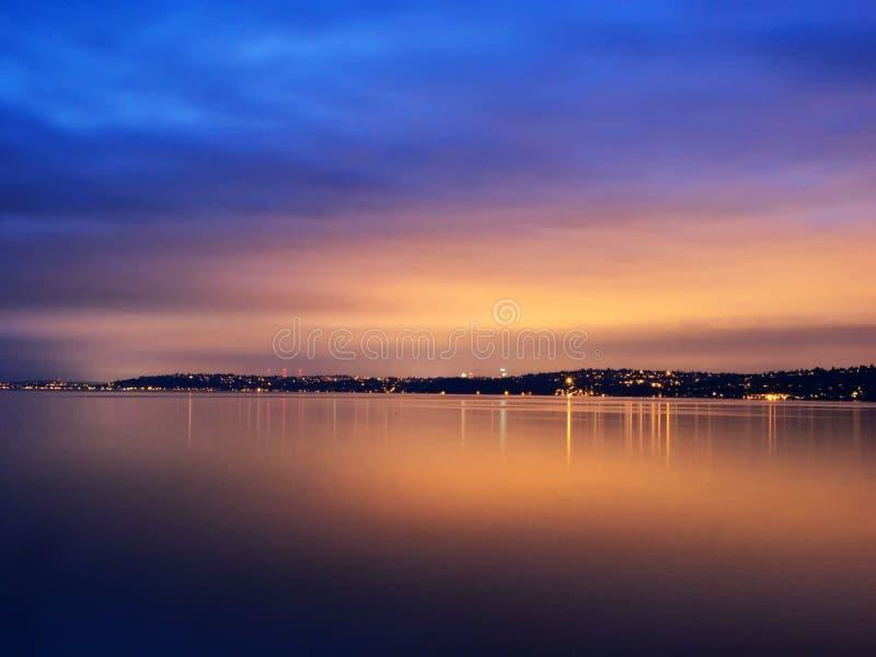 Por do sol e luzes urbanas refletidos na água imagem de stock