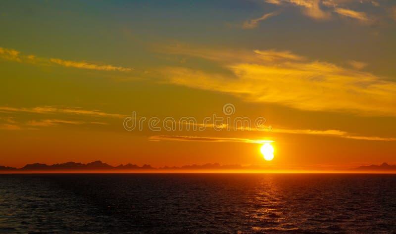 Por do sol e nascer do sol sobre o mar e o arquipélago de Lofoten da balsa de Moskenes - de Bodo, Noruega imagens de stock