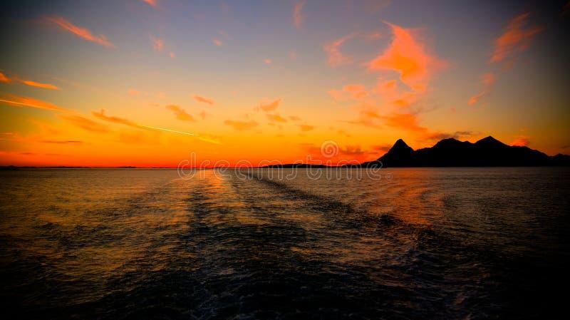 Por do sol e nascer do sol sobre o mar e o arquipélago de Lofoten da balsa de Moskenes - de Bodo, Noruega fotografia de stock