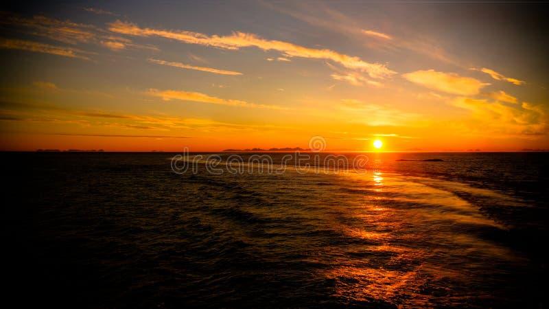 Por do sol e nascer do sol sobre o mar e o arquipélago de Lofoten da balsa de Moskenes - de Bodo, Noruega fotos de stock
