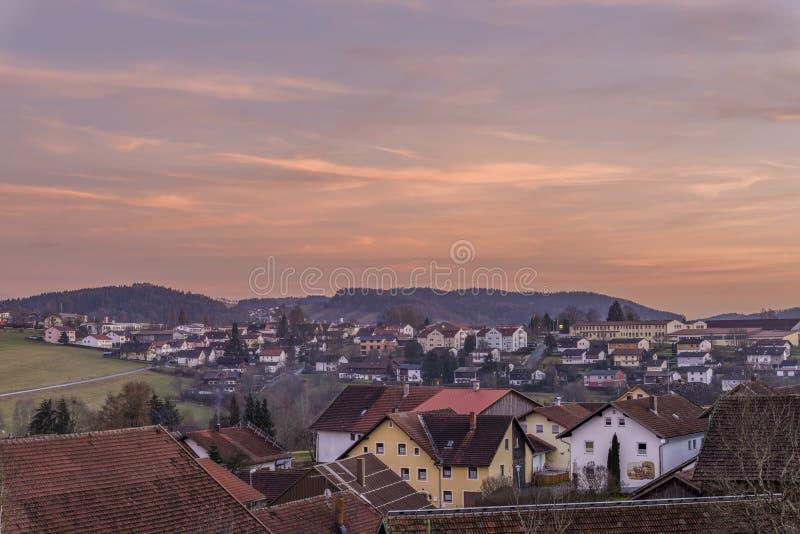 Por do sol e noite-vermelho na floresta bávara com vista da cidade Grafenau fotografia de stock royalty free