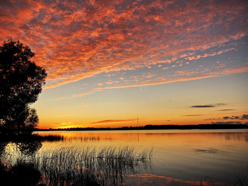 Por do sol e nuvens vermelhas no céu imagem de stock