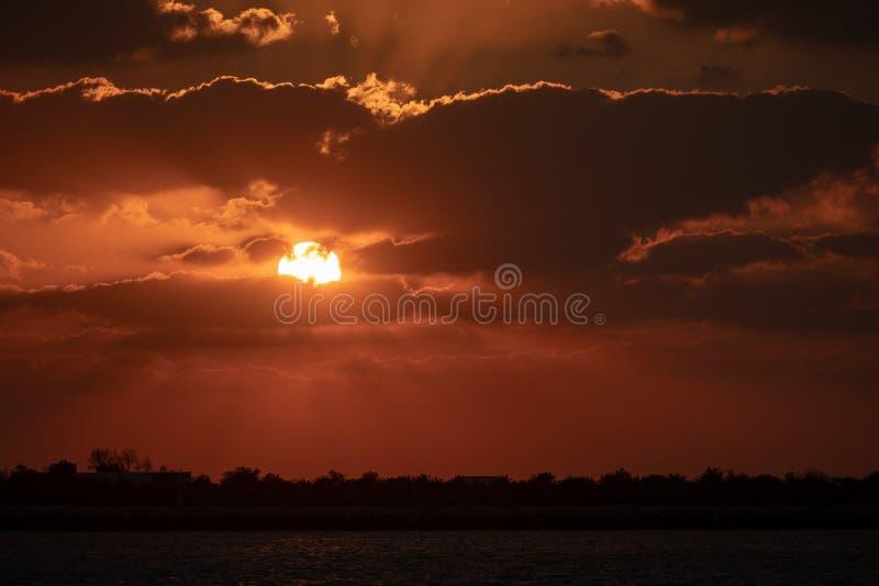 Por do sol e raios de sol de Dramaitc que repicam através das nuvens fotos de stock royalty free