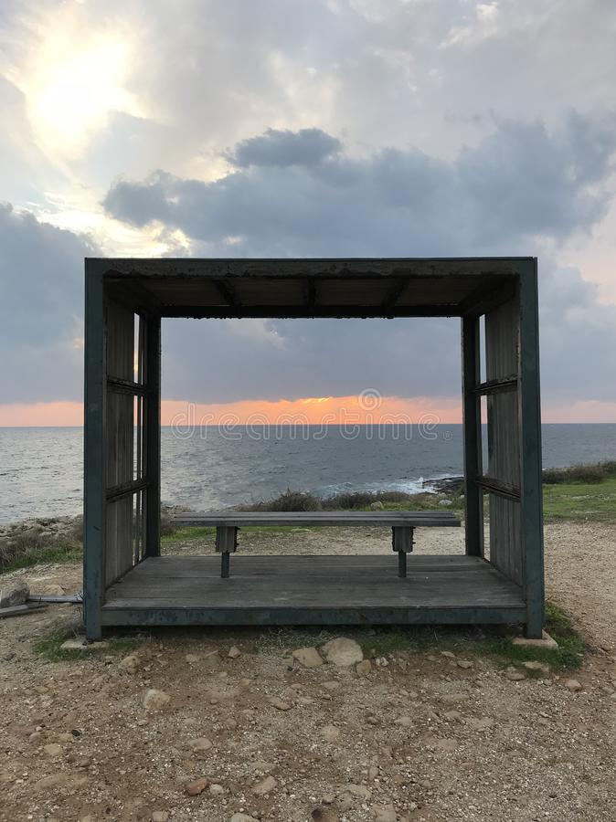 Por do sol e um banco em Paphos fotografia de stock