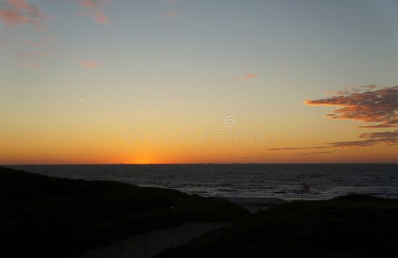 Por do sol em cima da praia aan de Wijk Zee fotografia de stock