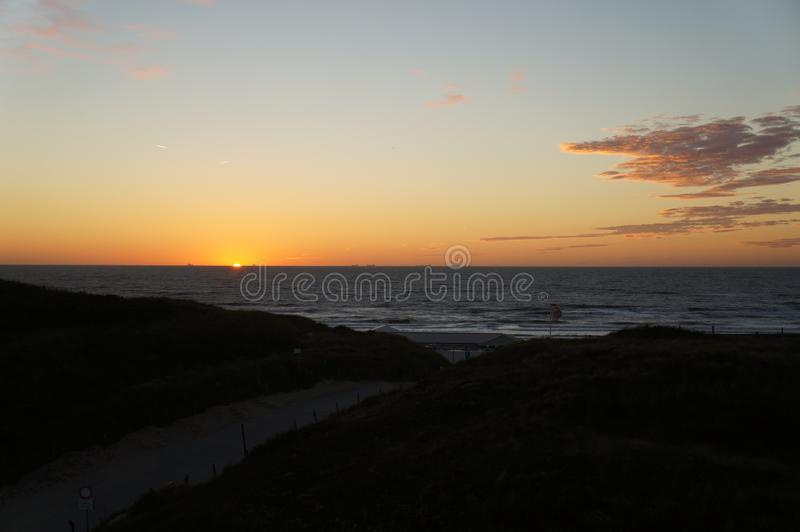 Por do sol em cima da praia aan de Wijk Zee foto de stock royalty free