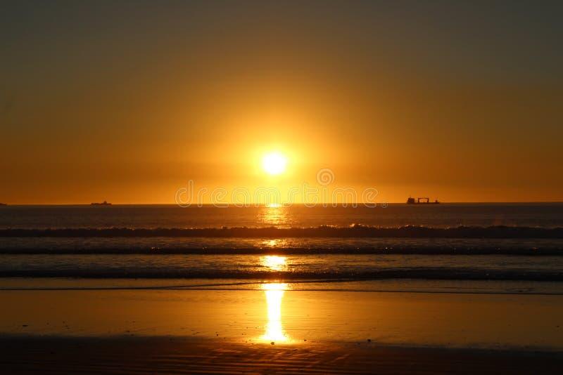 Por do sol em navios da praia de capetown no backround fotos de stock
