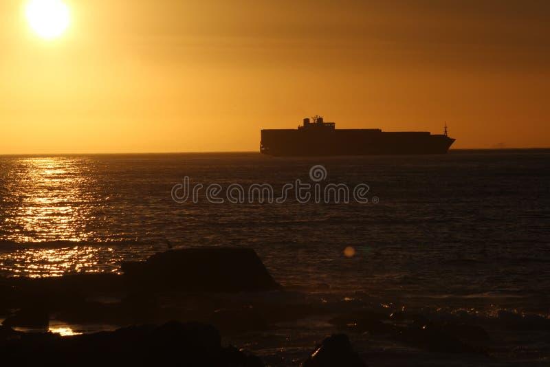 Por do sol em navios da praia de capetown no backround imagens de stock royalty free