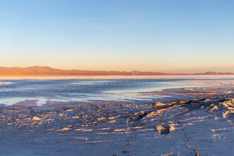 Por do sol em planos de sal de Uyuni em Bolívia, o deserto incrível de sal em Ámérica do Sul imagem de stock