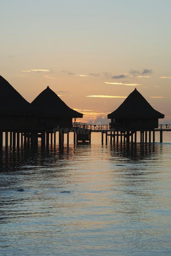 Por do sol em Polinésia sobre casas na água imagens de stock