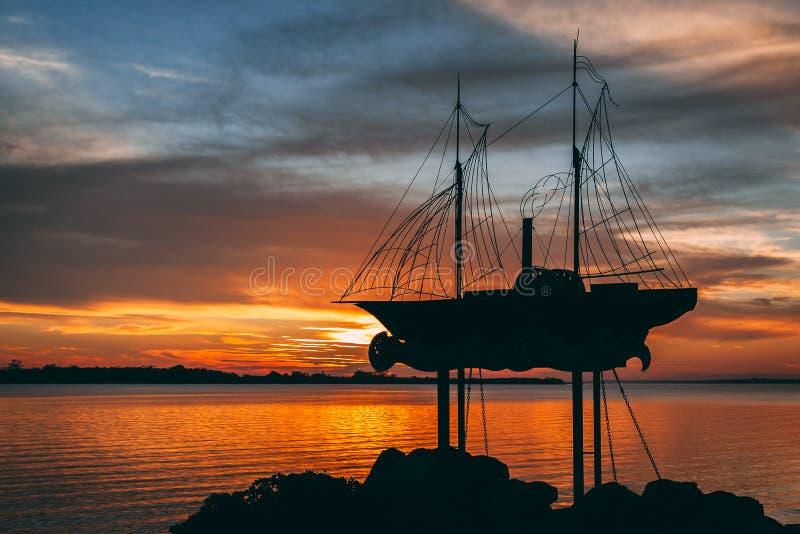 Por do sol em um lago com a estátua do objeto do barco fotos de stock