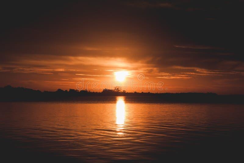 Por do sol em um lago com luz dourada foto de stock royalty free